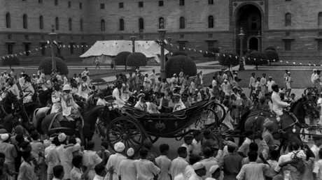 In this handout picture taken 15 August 1947, British Governor-General Lord Mountbatten (C) gestures as he rides in a carriage alongside Lady Edwina Mountbatten prior to witnessing the raising of the Indian tricolour for the first time at India Gate in New Delhi. © AFP