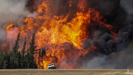 Smoke and flames from the wildfires erupt behind a car on the highway near Fort McMurray, Alberta, Canada, May 7, 2016. © Mark Blinch
