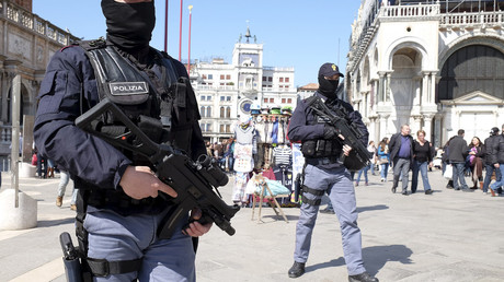 Italian masked police officers patrol in St. Mark's square in the Venice lagoon, Italy. © Manuel Silvestri