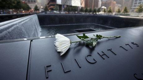 A single white flower is left on one of the panels containing the names of the victims of the attacks on the first day that the 9/11 Memorial was opened to the public at the World Trade Center site in New York, September 12, 2011. © Mike Segar