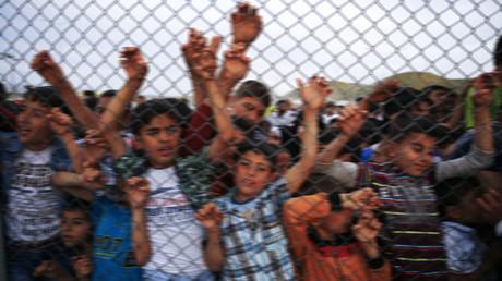 Refugee youths gesture from behind a fence at Nizip refugee camp near Gaziantep, Turkey. © Umit Bektas