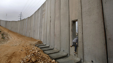 A Palestinian boy climbs through an opening in Israel's controversial barrier in Shuafat in the West Bank near Jerusalem. © Baz Ratner
