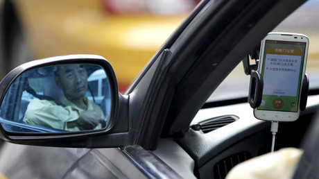 A taxi driver is reflected in a side mirror as he uses the Didi Chuxing car-hailing application in Beijing, China © Jason Lee