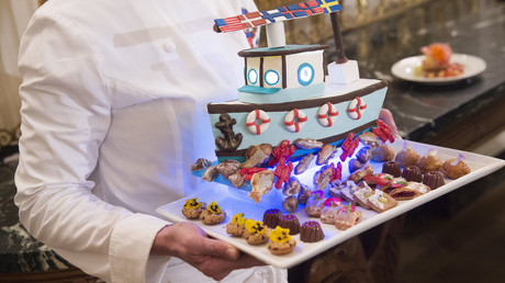 White House pastry chef Susie Morrison holds a dessert featuring a handcrafted fishing boat surrounded by miniature pastries during a press preview of a State Dinner in honor the Nordic countries in the State Dining Room of the White House in Washington, DC, May 12, 2016. © Saul Loeb