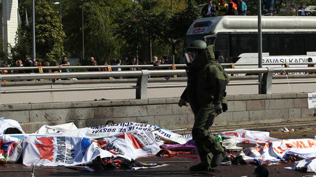 File photo: A bomb-disposal expert walks near victims' bodies covered with banners and flags, at the site of twin explosions near the main train station in Turkey's capital Ankara, on October 10, 2015. © Adem Altan