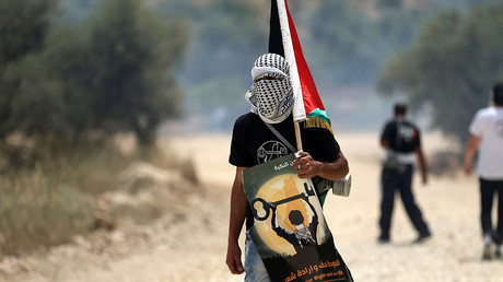 A masked protester holds a Palestinian flag during clashes with Israeli troops at a protest ahead of Nakba day, in the West Bank village of Bilin near Ramallah May  © Mohamad Torokman