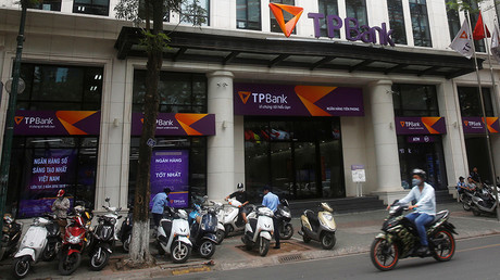 A man rides a motorcycle past the Vietnamese commercial Tien Phong bank in Hanoi May 13, 2016 © Kham
