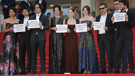 Director Kleber Mendonca Filho and cast members hold placards to protest against the impeachment of suspended Brazilian President Dilma Rousseff on the red carpet as they arrive for the screening of the film