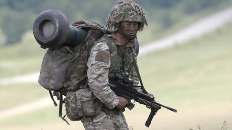 A British soldier on exercise walks across an area of Salisbury Plain, near to Westdown Camp, Britain © Peter Nicholls