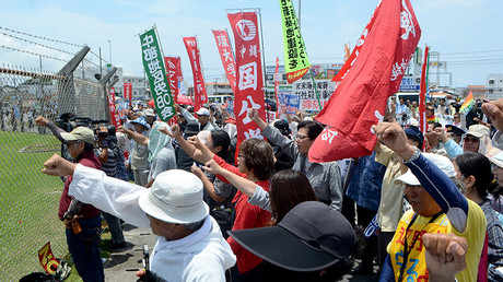 People raise their fists as they shout slogans to protest against the US military presence in front of the US Kadena Air Base in Cyatan, Okinawa prefecture, on May 21, 2016 © JIJI Press