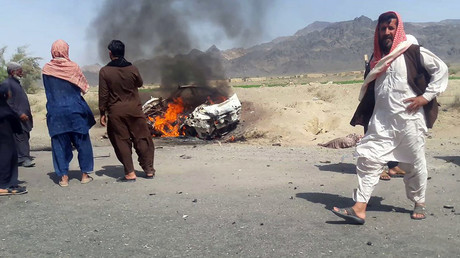Pakistani local residents gathering around a destroyed vehicle hit by a drone strike in which Afghan Taliban Chief Mullah Akhtar Mansour was believed to be traveling ©