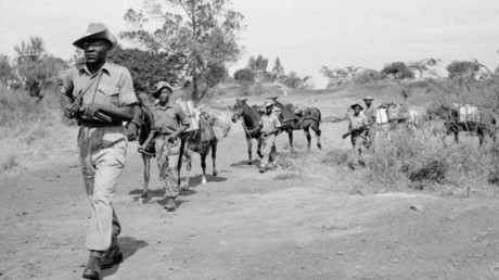 Troops of the King's African Rifles carry supplies on horseback. They are escorted by armed soldiers on watch for Mau Mau terrorists. © Wikipedia