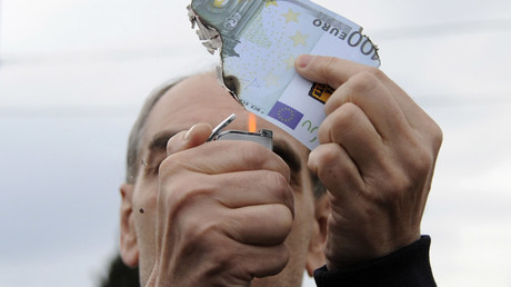 A protester burns a fake one hundred Euro banknote during a demonstration against a new package of tax hikes and reforms in Athens, Greece, May 22, 2016 © Michalis Karagiannis