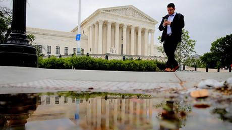 A pedestrian walks in front of the U.S. Supreme Court building in Washington, U.S. © Carlos Barria