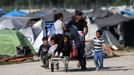 A man pushes a trolley with children sitting on it at the refugee and migrant makeshift camp on the Greek-Macedonia border near the village of Idomeni on May, 23 2016. ©Sakis Mitrolidis