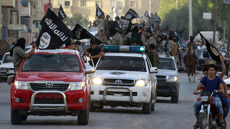 FILE PHOTO. Militant Islamist fighters waving flags, travel in vehicles as they take part in a military parade along the streets of Syria's northern Raqqa province. © Reuters