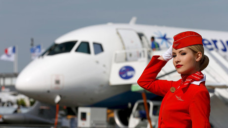 A cabin crew member of Russian carrier Aeroflot poses in front of a Sukhoi Superjet 100 airplane © Pascal Rossignol