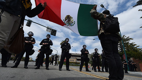 Protestors unfurl the Mexian flag before police outside the Anaheim Convention Center prior to a rally for the Republican presidential candidate Donald Trump on May 25, 2016 in Anaheim, California. © Mark Ralston