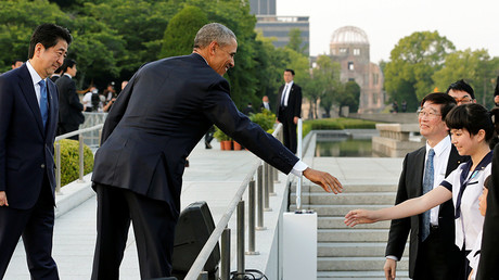 U.S. President Barack Obama (2nd L), flanked by Japanese Prime Minister Shinzo Abe, greets a school girl after delivering their speeches and laying wreaths in front 