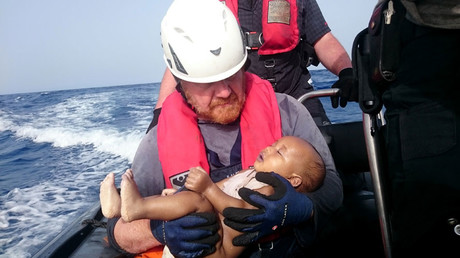 This handout photo released by German humanitarian NGO Sea-Watch shows a Sea-Watch crew member holding a drowned baby after a wooden boat transporting migrants capsized off the Libyan coast on May 27, 2016. © Christian Buttner
