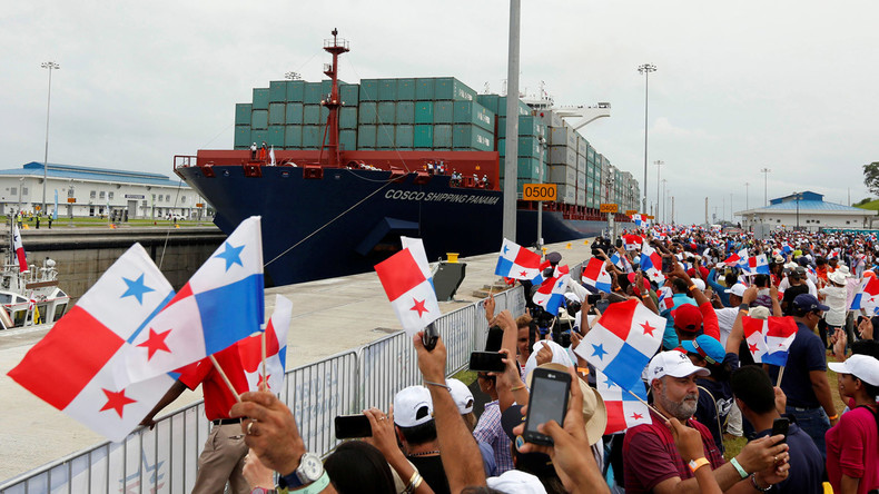 People wave Panama flags as the Chinese COSCO container vessel named Andronikos navigates through the Agua Clara locks during the first ceremonial pass through the newly expanded Panama Canal in Agua Clara, on the outskirts of Colon City, Panama June 26, 2016. © Carlos Jasso