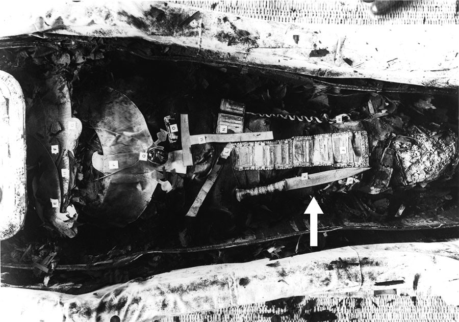 The mummy of King Tutankhamun. Black and white picture of Tutankhamun mummy showing the iron dagger (34.2 cm long) placed on the right thigh (arrowed)..© Griffith Institute, University of Oxford