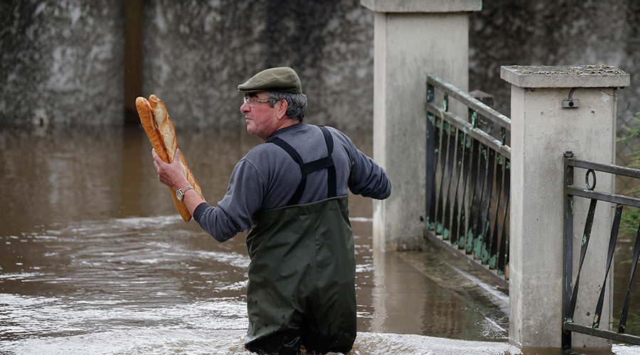 A resident brings baguettes to his mother's flooded house in Chalette-sur-Loing Montargis, near Orleans, France © Christian Hartmann