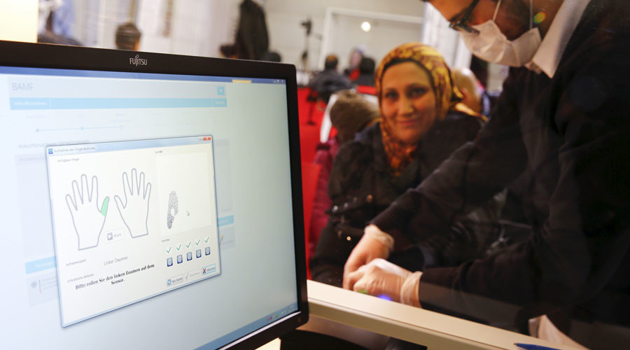 A Syrian woman gets her fingerprints taken at a registration centre in Herford, western Germany © Wolfgang Rattay