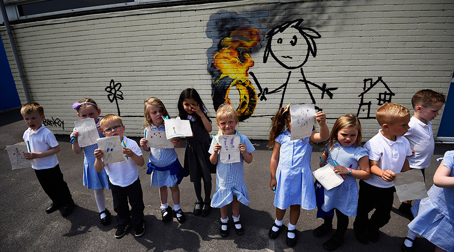 Reception class school children show off their drawings of a mural, attributed to graffiti artist Banksy, painted on the outside of a class room at the Bridge Farm Primary School in Bristol, Britain June 6, 2016 © Dylan Martinez