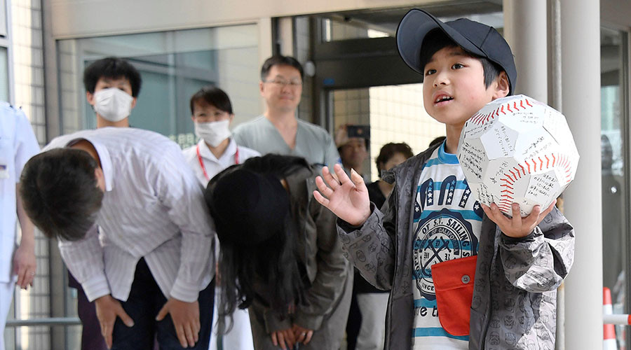 Seven-year-old Yamato Tanooka (R), who was found by authorities in the woods nearly a week after his parents abandoned him for disciplinary reasons, waves as he leaves a hospital while his parents bow in Hakodate on the northernmost Japanese main island of Hokkaido, Japan. ©Kyodo