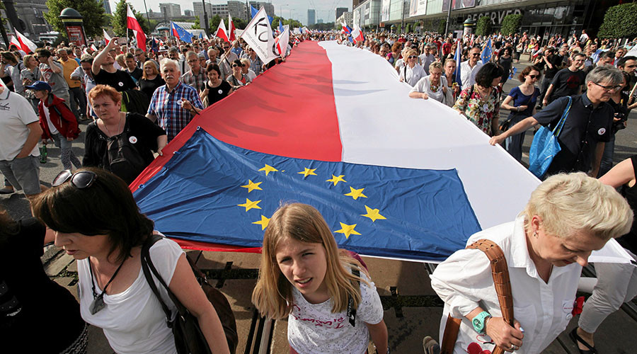 People hold giant Polish and EU flags as they take part in an anti-government demonstration organized on the 27th anniversary of the first free non-communist election, in Warsaw, Poland June 4, 2016. © Agencja Gazeta / Slawomir Kaminski