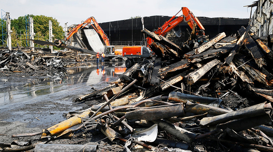 Power shovels remove debris from a burned down Duesseldorf Fair exhibition hall previously used as a home for asylum seekers and migrants in Duesseldorf, Germany, June 8, 2016 © Wolfgang Rattay