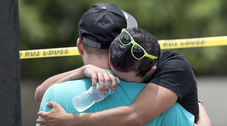 Supported by a friend, a man weeps for victims of the mass shooting just a block from the scene in Orlando, Florida, on June 12, 2016. © Gregg Newton