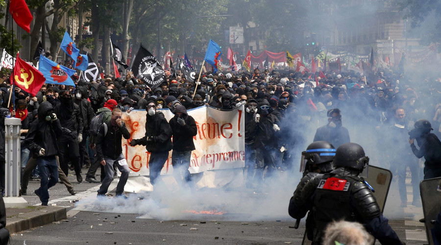 Masked youths with labour union flags are seen during clashes with French gendarmes and riot police during a demonstration in Paris as part of nationwide protests against plans to reform French labour laws, France, June 14, 2016. © Jacky Naegelen