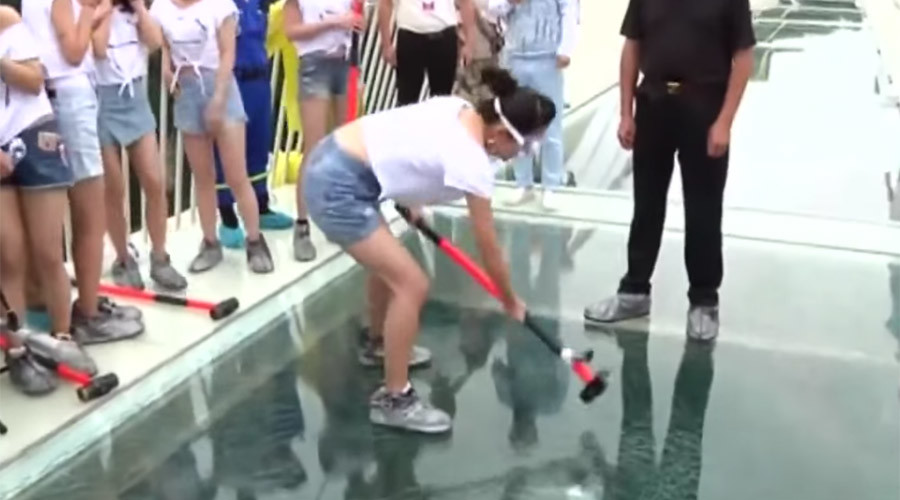 Daredevil volunteers test glass bridge safety in China - with sledgehammers (VIDEO)