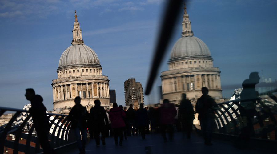 FILE PHOTO: People are silhouetted and reflected as they pass a view of St Paul's Cathedral on Millennium Bridge © Neil Hall