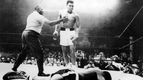 A picture taken May 26, 1965, in Lewiston, USA, during the world heavyweight boxing championship, at the end of which the American Muhammad Ali (Cassius Clay) (C) won against his compatriot Sonny Liston (L) after a one minute fight with Joe Walcott (R) as a referee. ©