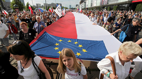 People hold giant Polish and EU flags as they take part in an anti-government demonstration organized on the 27th anniversary of the first free non-communist election, in Warsaw, Poland June 4, 2016 © Slawomir Kaminski