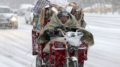 A man rides a motorcycle along a street in the snow in Altay, Xinjiang Uighur Autonomous region, China. © Reuters