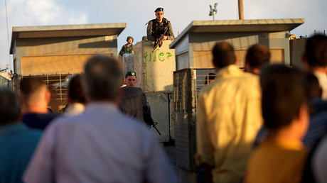 Israeli border police officers stand guard as Palestinians wait to cross through the Qalandia checkpoint to make their way to attend the first Friday prayer of the holy fasting month of Ramadan in Jerusalem's al-Aqsa mosque, near the West Bank city of Ramallah June 10, 2016 © Mohamad Torokman