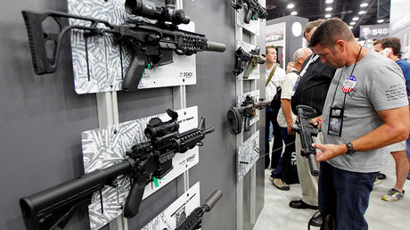 Gun enthusiasts look over Sig Sauers guns at the National Rifle Association's (NRA) annual meetings & exhibits show in Louisville, Kentucky, May 21, 2016 © John Sommers II