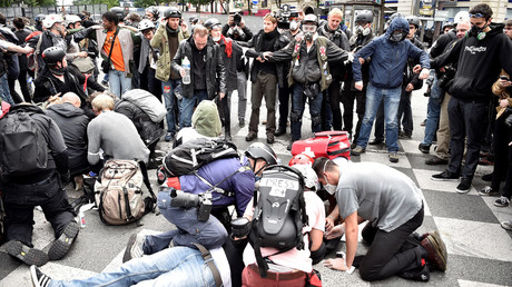 People gather around to assist an injured protester lying on the ground during a demonstration against proposed labour reforms in Paris on June 14, 2016. © Alain Jocard