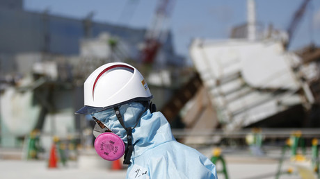 A Tokyo Electric Power Co. (TEPCO) employee, wearing a protective suit and a mask, walks in front of the No. 1 reactor building at TEPCO's tsunami-crippled Fukushima Daiichi nuclear power plant in Okuma town, Fukushima prefecture © Toru Hanai