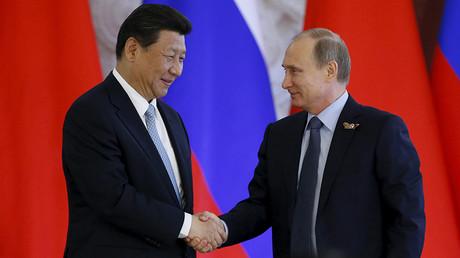 Russia's President Vladimir Putin (R) shakes hands with China's President Xi Jinping © Sergey Karpukhin