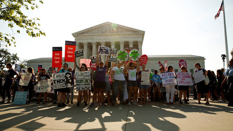 Demonstrators hold signs outside the U.S. Supreme Court as the court is due to decide whether a Republican-backed 2013 Texas law placed an undue burden on women exercising their constitutional right to abortion in Washington, U.S.  June 27, 2016. © Kevin Lamarque