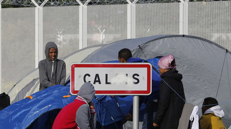 Migrants stand near a Calais city sign along a road near the makeshift camp called