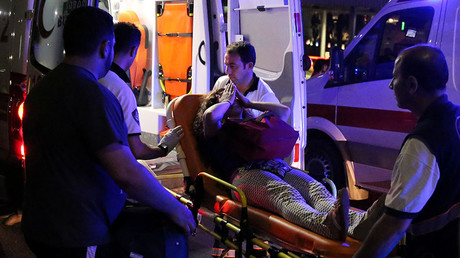 An injured woman covers her face as she is carried by paramedics into ambulance at Istanbul Ataturk airport, Turkey, following a blast June 28, 2016. © Goran Tomasevic