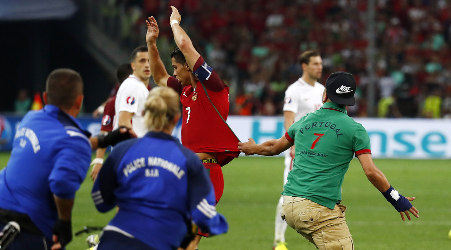 Fan invades the pitch during the game and grabs the shirt of Portugal's Cristiano Ronaldo. © Kai Pfaffenbach