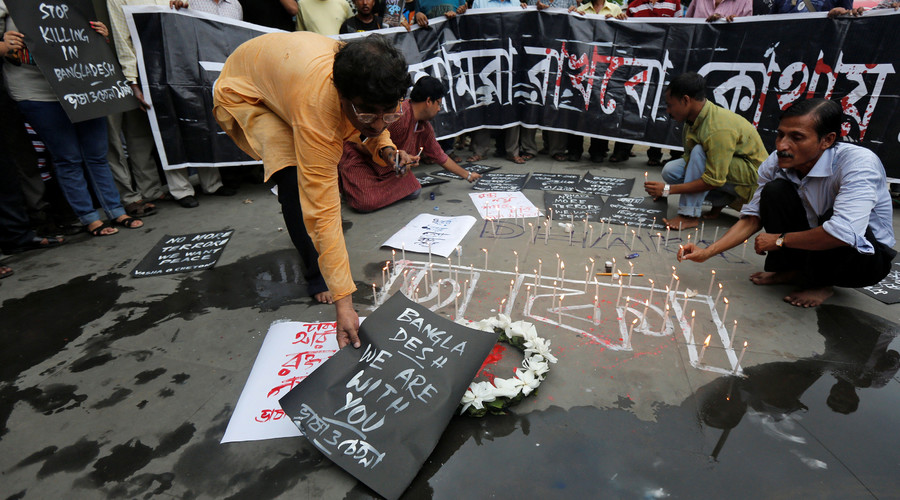 A man places a sign as others light candles during a vigil in Kolkata, India, to show solidarity with the victims of the attack at Holey Artisan restaurant after Islamist militants attacked the upscale cafe in Dhaka, Bangladesh, July 2, 2016. © Rupak De Chowdhuri