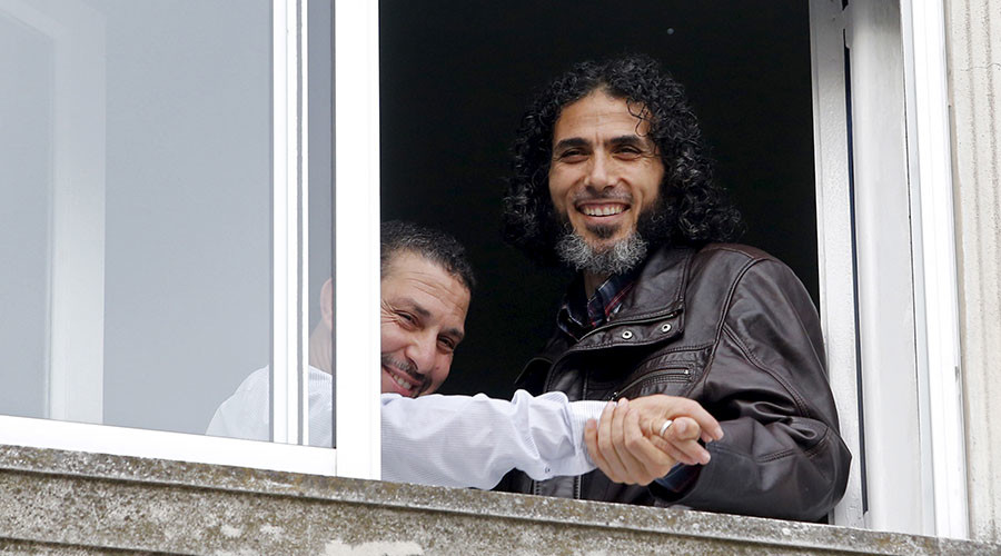 Former Guantanamo detainee Jihad Diyab (R) from Syria displays to the media the wedding ring of fellow ex-detainee Abdul Bin Mohammed Abis Ourgy of Tunisia, after the latter's wedding, at the window of Ourgy's apartment in Montevideo, June 5, 2015. © Andres Stapff